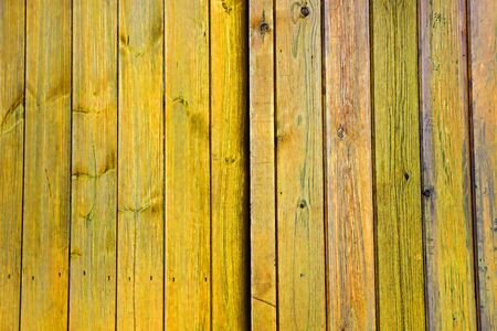 yellow ochre: Yellow faded wooden doors  planks  panels  vertical slats - Stripes Pattern as a Background Texture. Stock Photo