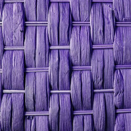 criss cross: Imaginative purple woven reed  wood abstract background texture. Stock Photo