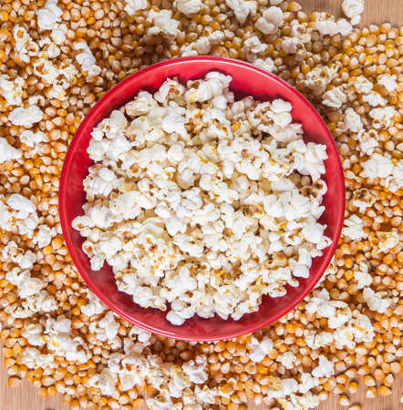 bowls of popcorn: Bowl of popcorn snacks, on wooden table with uncooked corn.