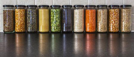 semilla: Health Food - semillas y legumbres en jarras, con reflexiones - lentejas, guisantes, cebada perlada, semilla de cilantro, pimienta negro, cuscús, maíz y arroz - panorama.