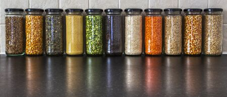 Health Food - seeds and pulses in jars, with reflections - lentils, split peas, pearl barley, coriander seed, black pepper, cous cous, corn, and rice - panorama.