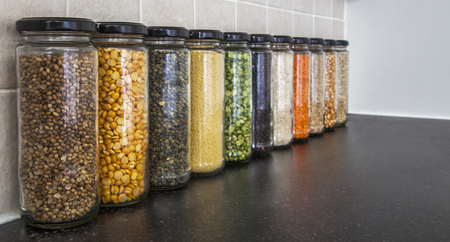 pulses: Health Food - herbs, seeds and pulses in spice jars - lentils, split peas, pearl barley, coriander seed, black pepper, cous cous, corn, and rice - panorama. Focus on closest jar, then fading, with copy  text space. Stock Photo