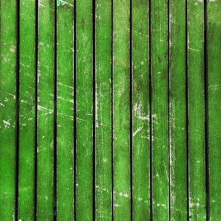 scuffed: Wonderfully beaten up, scratched and scuffed bright green wooden  planks  timber - vintage, abstract background texture, with peeling paint on wood. Stock Photo