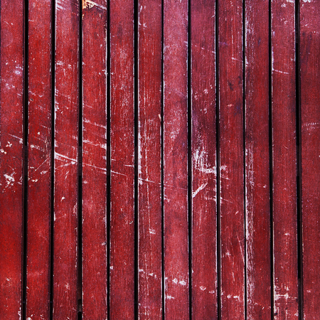 Wonderfully beaten up, scratched and scuffed red wooden  planks  timber - vintage, abstract background texture, with peeling paint on wood.