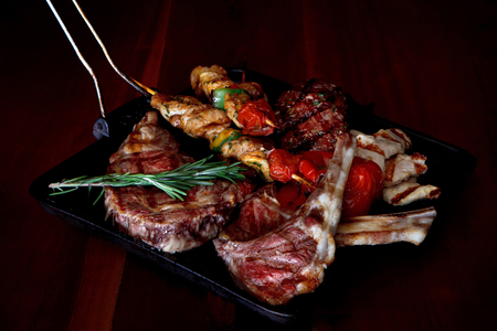 A mix of different types of meat grilled with rosemary and roasted vegetables.