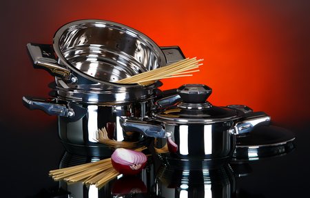 stewing: Empty pots and pans with raw vegetables and pasta on a dark background