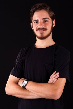 Young professional adult in black tshirt smiling and happy and content. Color expressive dramatic effect, dark and moody series. Studio shoot.