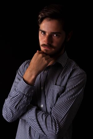 Young adult male looking sinister or contemplative. Color expressive dark and moody series. Concept image for corporate scheming. Hand under chin.