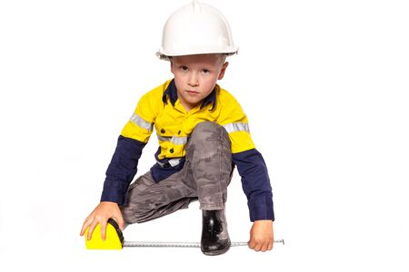 Young blond caucasian boy measuring something role playing as a construction worker in a yellow and blue hi-viz shirt, boots, white hard hat, and tape measure.