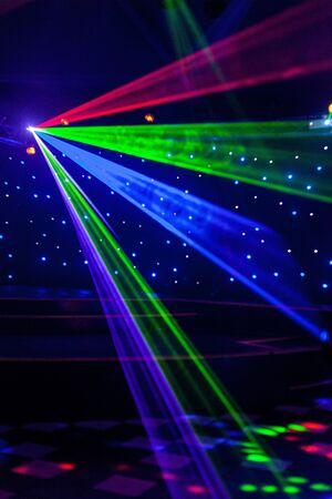 Club nocturno brillante luces láser rojas, verdes, moradas, blancas, rosas, azules que cortan el humo de la máquina de humo haciendo patrones de luz y arco iris en la pista de baile con bokeh de fondo. Mardi Gras Foto de archivo