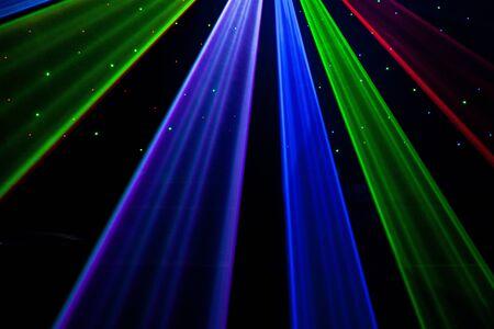 Bright nightclub red, green, purple, white, pink, blue laser lights cutting through smoke machine smoke making light and rainbow patterns on the dance floor with bokeh in the background. Mardi Gras or nightclub promo inspiration Stock fotó