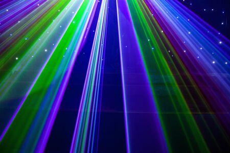 Club nocturno brillante luces láser rojas, verdes, moradas, blancas, rosas, azules que cortan el humo de la máquina de humo haciendo patrones de luz y arco iris en la pista de baile con bokeh de fondo. Inspiración de promoción de Mardi Gras o discoteca
