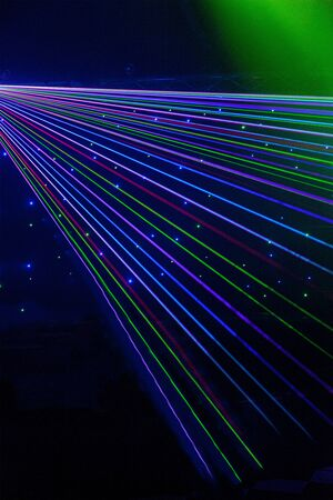 Bright nightclub red, green, purple, white, pink, blue laser lights cutting through smoke machine smoke making light and rainbow patterns on the dance floor with bokeh in the background. Mardi Gras or nightclub promo inspiration 免版税图像