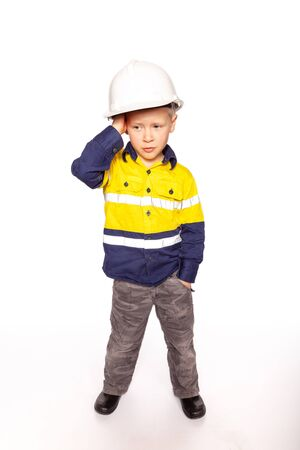 Young blond causacian boy scratching his head in disbelief role playing as a frustrated construction worker in a yellow and blue hi-viz shirt, boots, white hard hat, without hammer and tape measure.