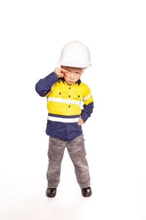 Young blond caucasian boy pointing out, with a fierce I'm watching you look role playing as a construction worker supervisor in a yellow and blue hi-viz shirt, boots, white hard hat, without a hammer and tape measure.