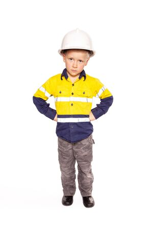 Young blond caucasian boy fists on hips role playing as an angry construction worker in a yellow and blue hi-viz shirt, boots, white hard hat, a hammer and tape measure.