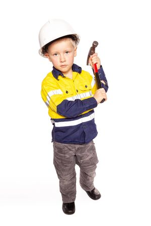 Young blond caucasian boy role playing as a construction worker in a yellow and blue hi-viz shirt, boots, white hard hat, a red hammer without tape measure.
