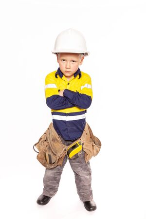 Young blond caucasian boy arms folded role playing as an angry construction worker in a yellow and blue hi-viz shirt, boots, white hard hat, tool belt, a hammer and tape measure.
