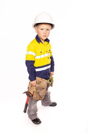 Young blond caucasian boy looking out with a fierce look role playing as a construction worker supervisor in a yellow and blue hi-viz shirt, boots, white hard hat, tool belt, a hammer and tape measure.