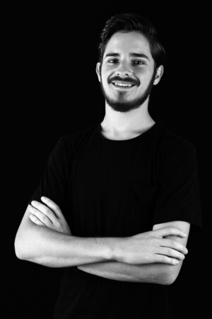 Young professional adult in black tshirt smiling and happy and content. Monotone, black and white for  expressive dramatic effect, dark and moody series. Studio shoot.