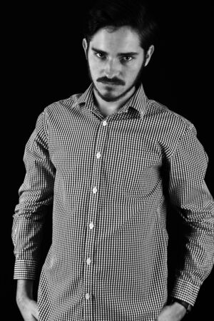 Young adult male looking sinister or contemplative. Monotone, black and white for dramatic effect, dark and moody series. Concept image for corporate scheming. Hand in pockets looking into camera