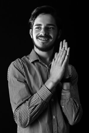 Young professional adult smiling and happy and content rubbing hand in success or scheming. Monotone, black and white for dramatic effect expressive dramatic effect, dark and moody series. Concept for achievement. Imagens