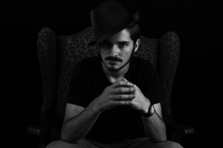Close up of young adult male looking sinister or contemplative. Monotone, black and white for dramatic effect, dark and moody series. Concept image for magician in wingback chair unhappy and scheming. Stock Photo