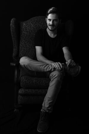 Young caucasian adult man sitting relaxed in wingback chair with sardonic and knowing smile on his face. Monotone, black and white for dramatic effect, dark and moody series. Concept image for mystery man. Stockfoto