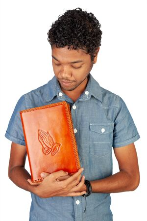 Young Indo-Mauritian or Creole Pastor in training holding a bible lovingly. Portrait format isolated on white background. Inspiration for poster with copy space for devotion, prayer circle or faith.