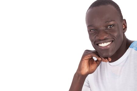 Close up of handsome young Sudanese man face to camera in white tshirt smiling with white teeth showing joy pleasure and confidence in landscape format with copy space isolated on white background. Reklamní fotografie