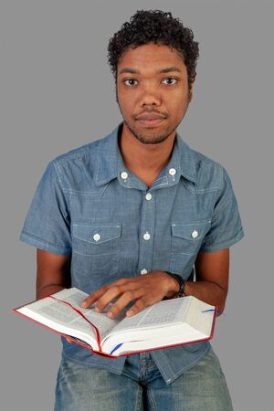 Young Indo-Mauritian or Creole Pastor in training holding an open bible pointing to words on the page. Portrait format isolated on grey background. Poster with copy space for prayer circle advertise.