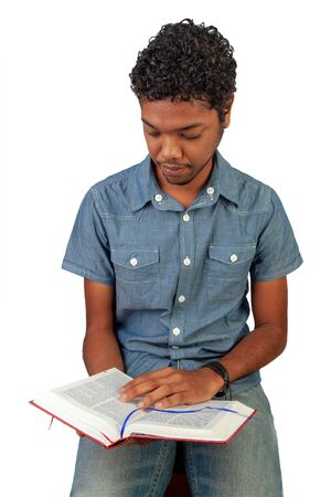 Young Indo-Mauritian or Creole Pastor in training holding an open bible looking at the page. Portrait format isolated on white background. Inspiration for poster with copy space for devotion, prayer. 版權商用圖片