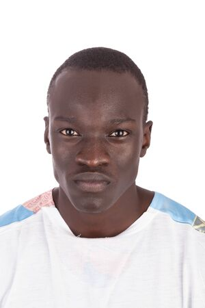 Young handsome Sudanese man with bland expression piercing eye contact face to camera in white tshirt in portrait format with copy space isolated on white background metaphor for help me please