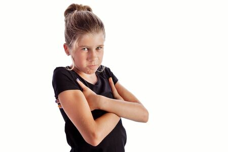 Young girl with black shirt isolated on white background with hands under arms in closed angry pose. Inspiration for meme or mother I dont like you pose 版權商用圖片