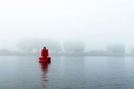 Red buoy in a river in the mist