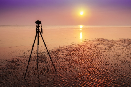 An abandoned camera and tripod by the beach on sun set Stock Photo