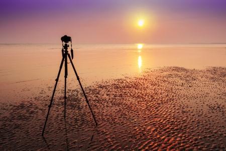 Una cámara y un trípode abandonado en la playa en puesta del sol