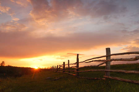 Spring sunset with a wooden fence photo
