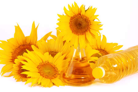 Sunflowers and  glass pitcher with sunflower oil   isolated on white background photo