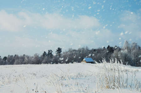 Winter landscape with a lone house and snowfall photo
