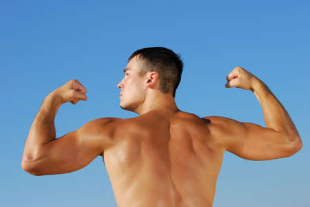 Muscular young man, outdoor shot on sky background photo