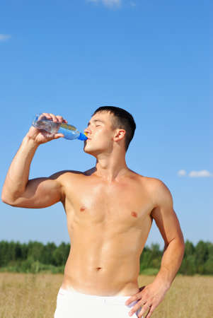 man drinking water: Portrait of young man drinking water after training Stock Photo