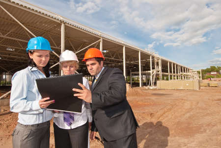 construction plans: Director and engineers on construction site of shopping center