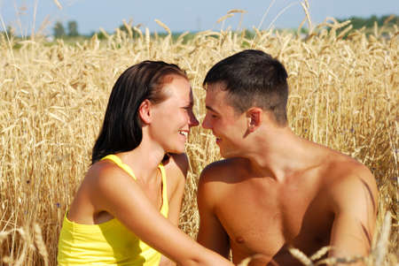 Young couple kissing on wheat field Stock Photo - 10425234