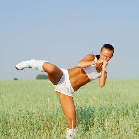 kicking: Young attractive woman doing morning sports exercises
