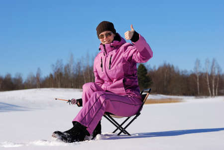 Young attractive girl on winter fishing