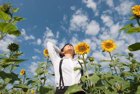 Young adult  woman relaxation on  sunflowers field photo