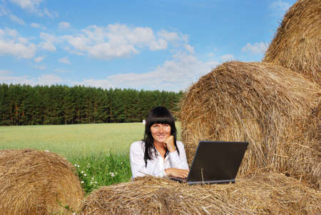 Young attractive girl with  laptop on  agricultural field photo