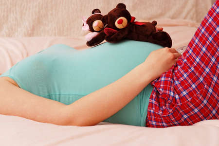 Young pregnant mother lies with soft toy of their future baby on last month of pregnancy