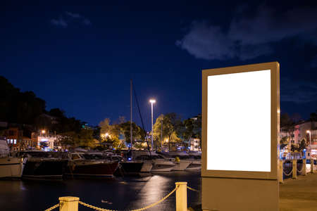 An empty billboard for advertisement. By the sea, in the night with several boats and yachts behind it. Clear blue sky and long exposure lights on the surface of the Marmara sea.